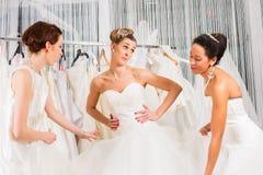 Kvinnor som har gyckel under brud- klänningmontering shoppar in Royaltyfri Foto
