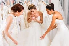 Kvinnor som har gyckel under brud- klänningmontering shoppar in Royaltyfria Foton