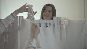Kvinnor som har gyckel under montering för brud- kappa i bröllopmodelager lager videofilmer