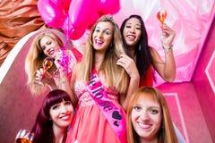 Kvinnor som har ungmöpartiet i nattklubb Royaltyfri Bild