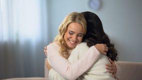 Kvinnor som hemma sitter och att le och krama lyckligt, goda nyheter, kamratskap stock video