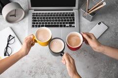 Kvinnor som i regeringsställning rymmer koppar kaffe över tabellen arkivfoto
