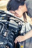 Kvinnor som kontrollerar bilmotorn för, går turen royaltyfri bild