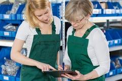 Kvinnor som kontrollerar produktlistan Arkivfoton