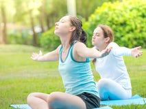 Kvinnor som kopplar av med yoga parkerar in Arkivfoton