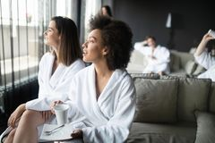 Kvinnor som kopplar av och dricker te i ämbetsdräkter under wellnesshelg royaltyfria bilder