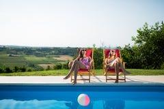 Kvinnor som kopplar av och solbadar arkivfoto