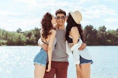Kvinnor som kysser le mannen på stranden på sommardag Royaltyfria Bilder