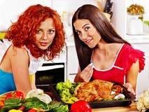 Kvinnor som lagar mat höna på kök. Arkivfoto