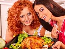 Kvinnor som lagar mat höna på kök Arkivfoto