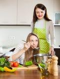 Kvinnor som lagar mat något med grönsaker Arkivfoto