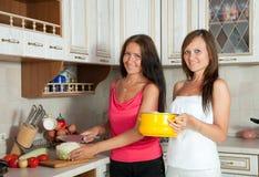 Kvinnor som lagar mat på dem kök Arkivbild