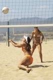 Kvinnor som leker volleyboll på strand Arkivbild