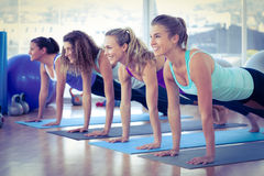 Kvinnor som ler, medan göra plankan, poserar i konditionmitt Royaltyfri Bild