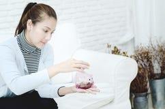 Kvinnor som ler, och rosa myntkrus i hand arkivfoton