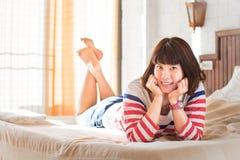 Kvinnor som ligger på säng med leendeframsidan Royaltyfria Bilder