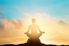 Kvinnor som mediterar på det höga berget i solnedgångbakgrund arkivfoto