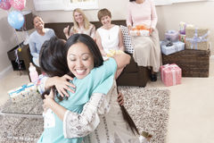 Kvinnor som omfamnar på baby shower Arkivbild