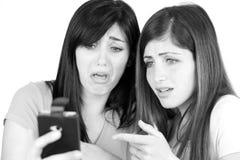 Kvinnor som oroas och förskräckas av översittaretextmeddelandet på smartphonen arkivbilder