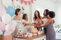 Kvinnor som rostar med fruktsafter på baby showerpartiet royaltyfria bilder