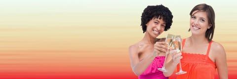Kvinnor som rostar mot oskarp röd och persikabakgrund Arkivfoto