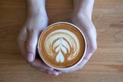 kvinnor som rymmer kaffekoppen, trätabellkafé, medan ha coffe royaltyfria bilder