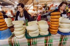 Kvinnor som säljer hemlagad och rökt ost på stor matmarknad Arkivbild