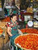 Kvinnor som säljer nya grönsaker Arkivfoto