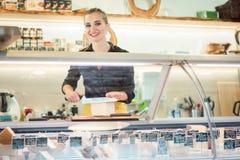 Kvinnor som s?ljer ost p? r?knaren i en supermarket royaltyfri fotografi
