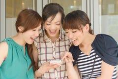 Kvinnor som ser något på en mobiltelefon Fotografering för Bildbyråer