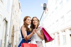 Kvinnor som shoppar och tar selfie vid smartphonen Arkivfoto