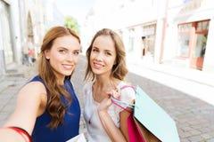 Kvinnor som shoppar och tar selfie vid smartphonen Arkivbild