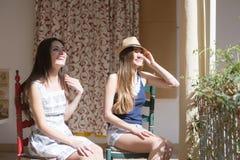 Kvinnor som sitter på balkong och att le Arkivbild