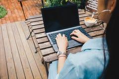 Kvinnor som skriver på kaffe för bärbar datordator Arkivbild