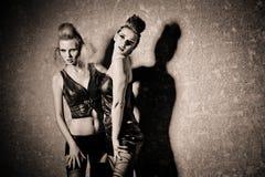 Kvinnor som slitage korsetten och poserar på väggbakgrund royaltyfri foto