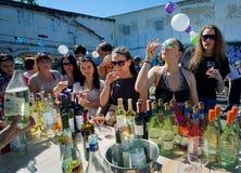 Kvinnor som smakar vitt vin i utomhus- stång Royaltyfria Bilder