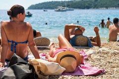 Kvinnor som solbadar i strand på Adriatiskt havet Dubrovnik Royaltyfri Fotografi