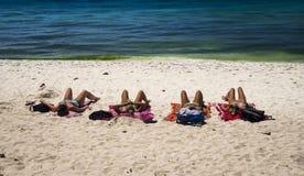 4 kvinnor som solbadar på stranden Arkivfoto