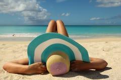 Kvinnor som solbadar på stranden med krökningen, lägger benen på ryggen Arkivbild
