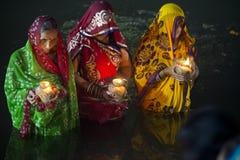 Kvinnor som står i flodvatten på chhatpujaen Royaltyfria Foton