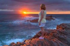 Kvinnor som står på den steniga stranden på härlig soluppgång Arkivbild