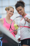 Kvinnor som stås på den netto tennisbanan Royaltyfria Foton