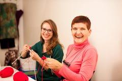Kvinnor som sticker med röd ull Eldery kvinna som överför hennes knowl Arkivfoto