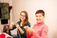 Kvinnor som sticker med röd ull Eldery kvinna som överför hennes knowl Royaltyfria Foton