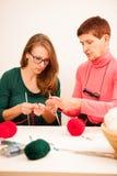 Kvinnor som sticker med röd ull Eldery kvinna som överför hennes knowl Royaltyfri Foto