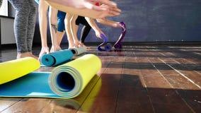 Kvinnor som sträcker och kopplar av i yogagrupp stock video