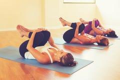 Kvinnor som sträcker och kopplar av i yogagrupp Fotografering för Bildbyråer