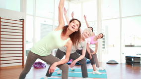 Kvinnor som sträcker på en yogagrupp lager videofilmer