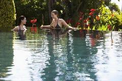 Kvinnor som talar i utomhus- simbassäng Arkivbild