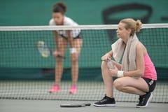 Kvinnor som tar avbrottet på tennisbanan Fotografering för Bildbyråer